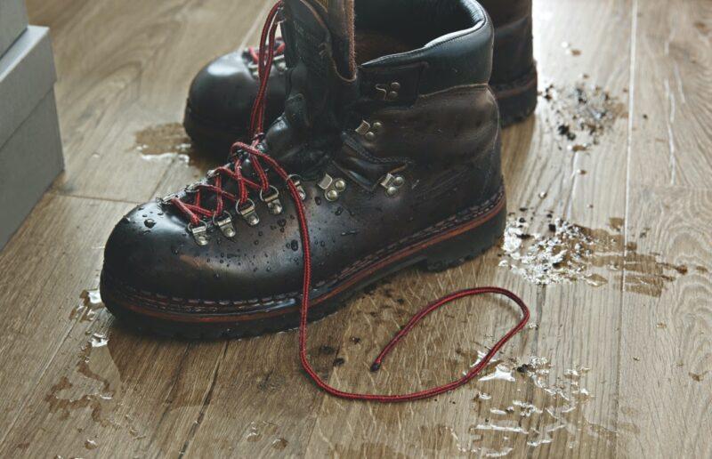scarpe sporche su pavimento in legno